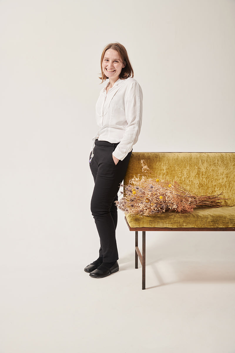 A white woman smiles at the camera. Her hands are in her pockets. She is wearing a white shirt with concealed openings at her arms and chest. A tube rests on her stomach. The back ground is white, she is leaning on a. crushed velvet, moss coloured sofa. There is a bunch of dried flowers on the sofa next to her.