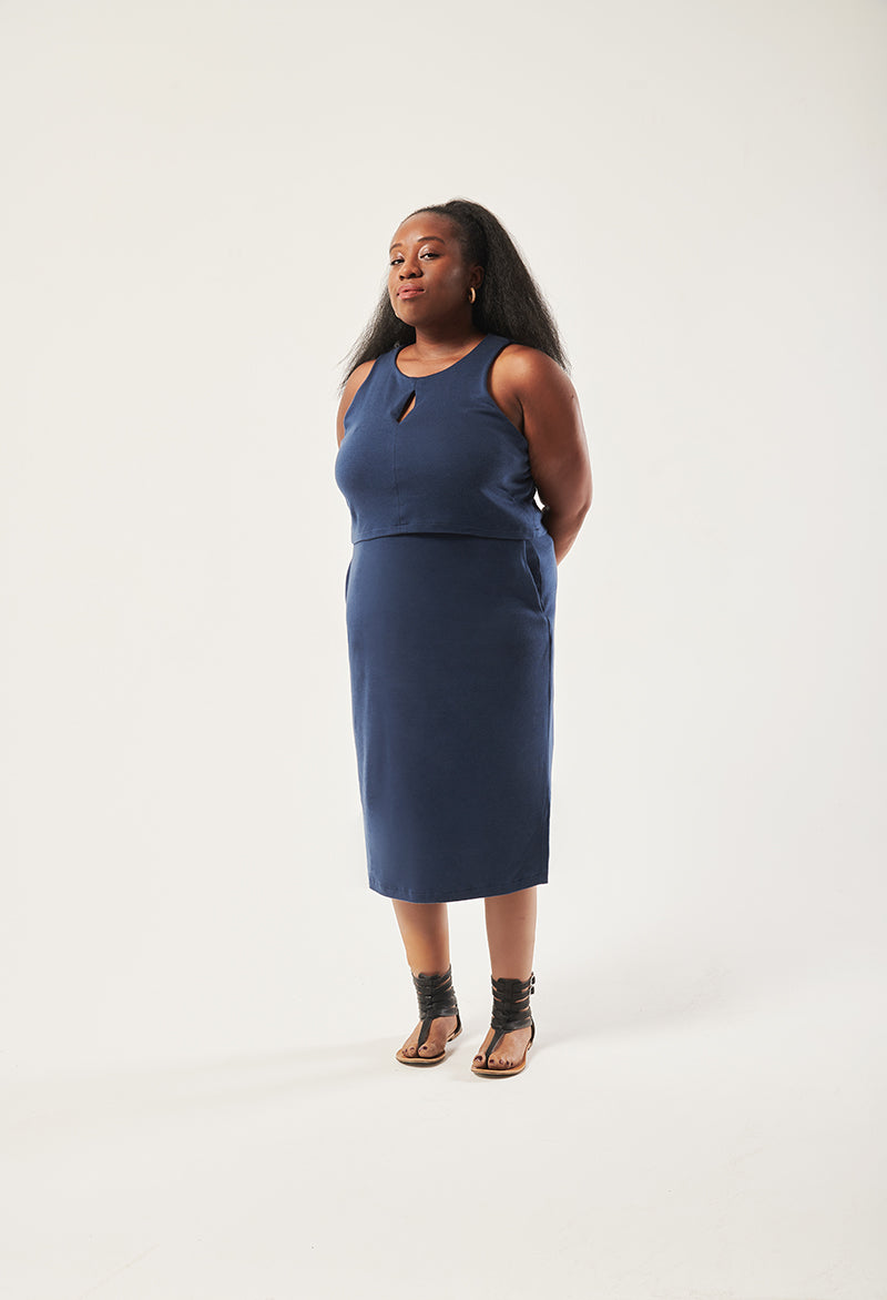 A black woman looks in to the camera. She is wearing a navy dress that is sleeveless with a front keyhole opening at the chest and pockets. Her arms are behind her back. Her legs are prosthetic and have a flat sandal shoe on them.
