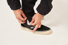 Load image into Gallery viewer, A close up of the hem of a pair of trousers. His hands are pulling open the invisible hem zip. He is wearing white socks and plimsolls and the cuffs of his black silk shirt are visible.