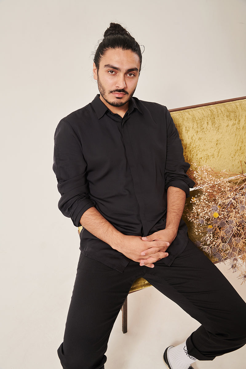 A south Asian man with long dark hair in a bun looks serenely in to the camera. He is wearing a bamboo silk shirt rolled to the elbows, and black trousers that are rolled at the hem. He is sitting on a crushed velvet moss coloured sofa, with some dried flowers on the seat to his right. The background is white.