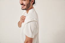 Load image into Gallery viewer, A south Asian man is laughing off camera, the top of his head is cropped. He is pulling up part of the wrap sleeve on his white t-shirt. The background is white. There is a zip pulled open on his chest for port access.