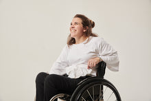 Load image into Gallery viewer, A woman with brown hair is smiling at the top left of the image.  Her left arm is resting on the back of her manual wheelchair. She is wearing a white adaptive wrap top  with winged sleeves.  She is wearing black seated adaptive trousers.