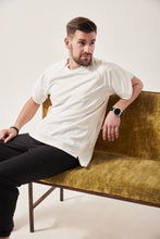 Load image into Gallery viewer, A white man with styled dark brown hair looks to the right. He is reclining on a crushed velvet moss coloured sofa. He is wearing a white t-shirt with wrap sleeves and concealed front zips to allow chest access. His left arm is resting on the back of the sofa and he has a large black watch on.