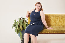 Load image into Gallery viewer, A white woman with dark blonde hair in a centre parting looks in to the camera. She is wearing a navy sleeveless dress that has a keyhole opening below the neckline. A tube comes from a hidden opening at her waste. Her left arm rests on the back of a crushed velvet moss coloured sofa. There is a fern plant on her right (left of the flat image) against a white background.