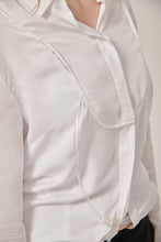 Load image into Gallery viewer, Close up of a woman's white shirt. There is a bib styling detail that conceals a chest opening. A tube comes from the woman's waist and loops back in at the chest.