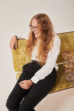 Load image into Gallery viewer, A woman with curly blonde hair laughs whilst looking off to the left of the frame, She has a white silk shirt on that has concealed sleeve openings, and a pair of black seated trousers with an adjustable wrap front. She is sitting on a crushed velvet sofa and the edge of a bunch of dried flowers is behind her.
