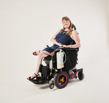 Load image into Gallery viewer, A smiling woman with dark blonde hair sits on an electric wheelchair in the centre of the image. She has a pink hairband on and black sandals with red bows on her feet. She is wearing a navy sleeveless dress, a tube comes from an opening at her waist.