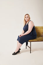 Load image into Gallery viewer, A woman with blue eyes and blonde hair looks above up off frame. She is wearing a navy sleeveless dress with a split in the hem.A pocket is visible beneath her elbow. She sits on a crushed velvet sofa that is moss coloured. She has flat black shoes one. The background is white.