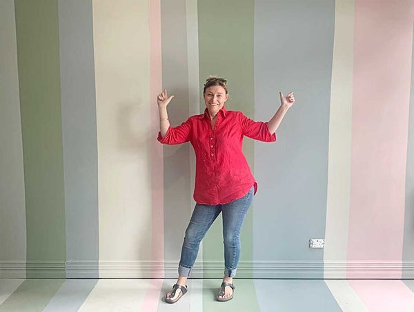 A photo a Plain Jane in front of a pastel green, blue, white and pink wall, painted with Autentico paints.
