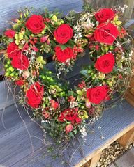 red heart shaped funeral wreath made from roses