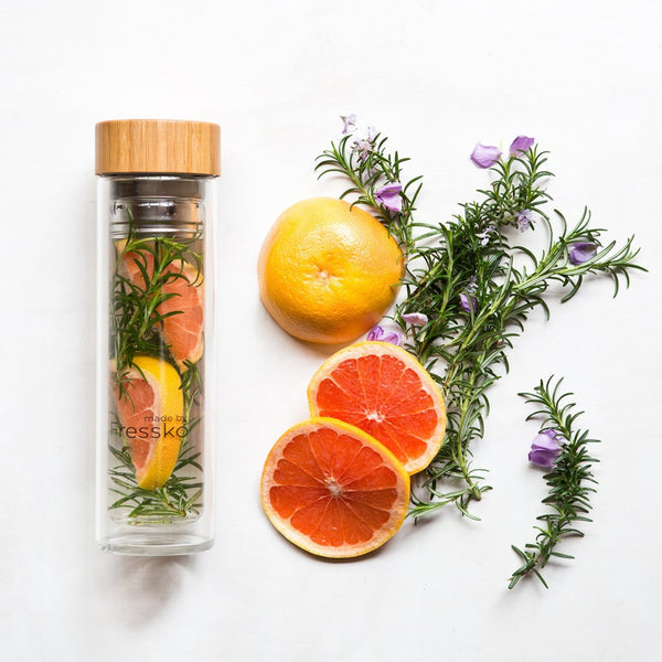 Glass Fressko flask filled with water infusion, grapefruit and rosemary surrounding