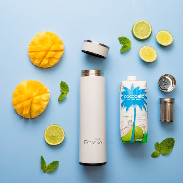 White Fressko flask surrounded by mango lime and coconut water