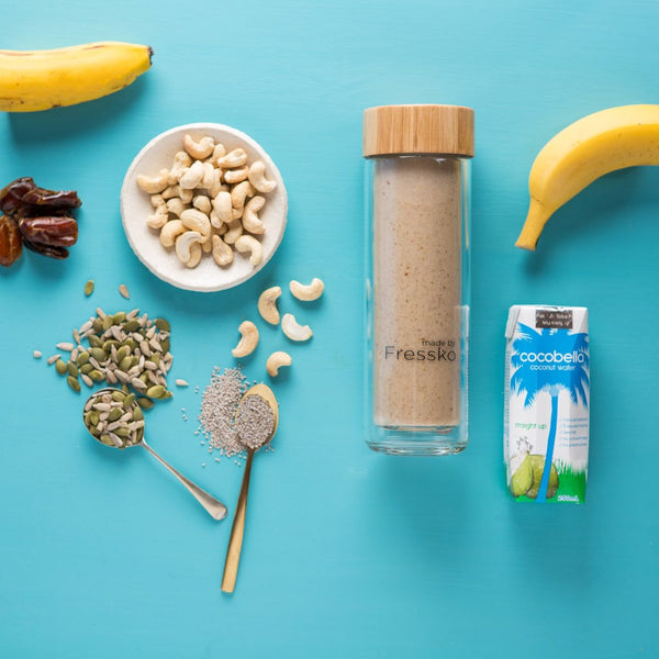 Fressko flask filled with smoothie surrounded by banana, cashews, seeds, dates and coconut water