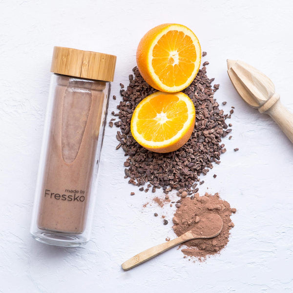 Glass fressko flask filled with jaffa smoothie surrounded by orange and cacao nibs