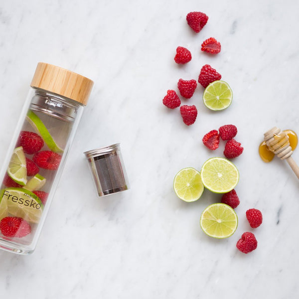 Raspberry and Lime infused water inside fressko flask surrounded by raspberries and limes