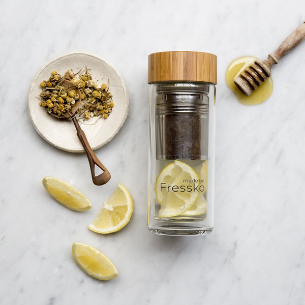 Lemon and honey chamomile tea in glass flask surrounded by lemon honey and chamomile