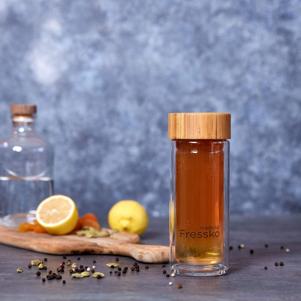 Spiced shandy mocktail inside fressko glass flask surrounded by spices and lemons
