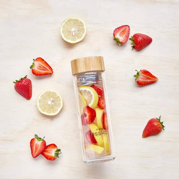 Fruit water inside flass flask surrounded by strawberry and lemon