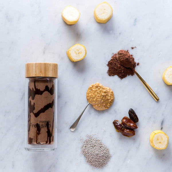 Snickers smoothie in glass fressko flask surrounded by ingredients