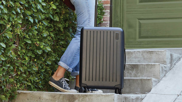 Girl holding black suitcase on stairs