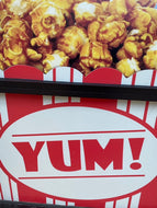 Yum! on a sign in store window with caramel popcorn on top