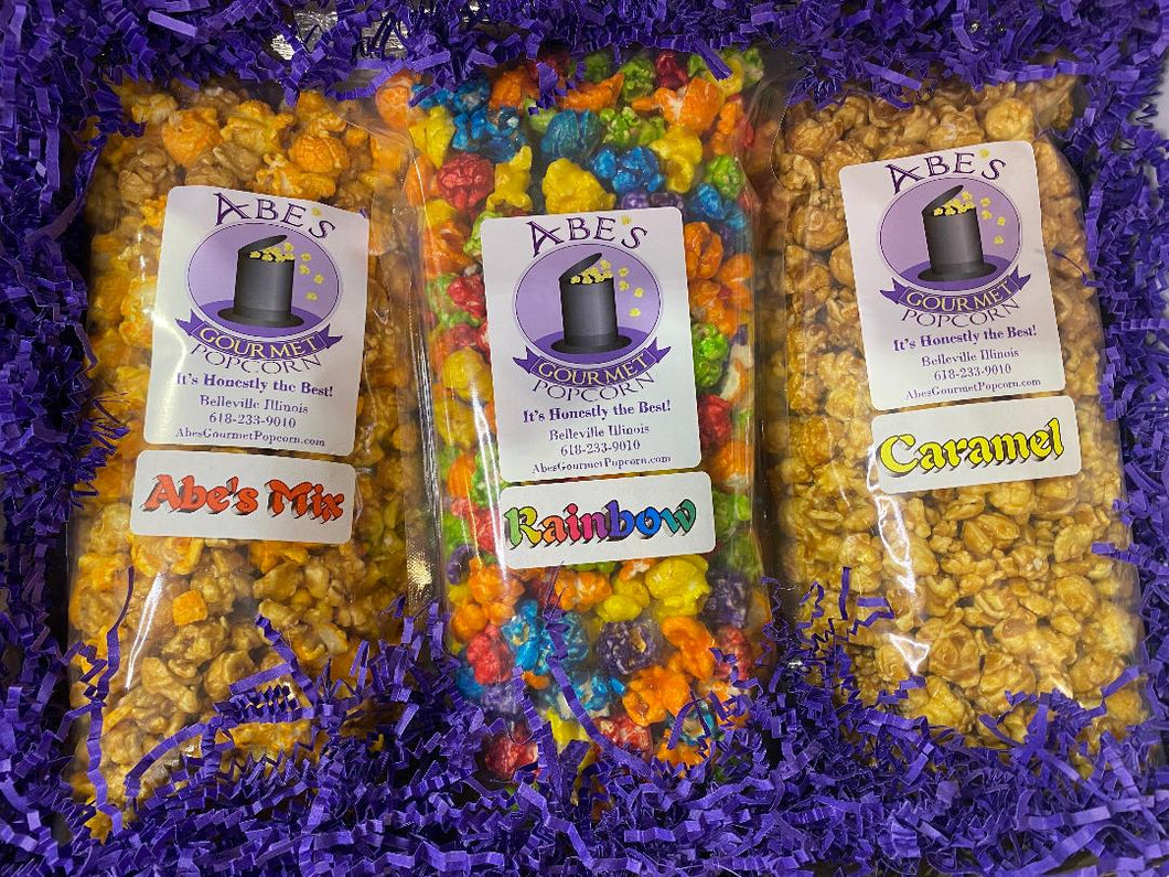 Inside of the Mix it Up  Gourmet popcorn gift box showing the 3 bags of popcorn in shredded crinkle paper