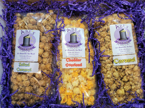Contents of Cheddar Between the Sweets popcorn gift box.  1 bag of Salted Caramel popcorn, 1 bag of Cheddar Overload popcorn and 1 bag of Caramel popcorn.  All surrounded by paper crinkles and wrapped in tissue paper to make opening an experience.