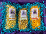 Inside of classic popcorn box showing bags of caramel popcorn, white cheddar popcorn and cheddar popcorn