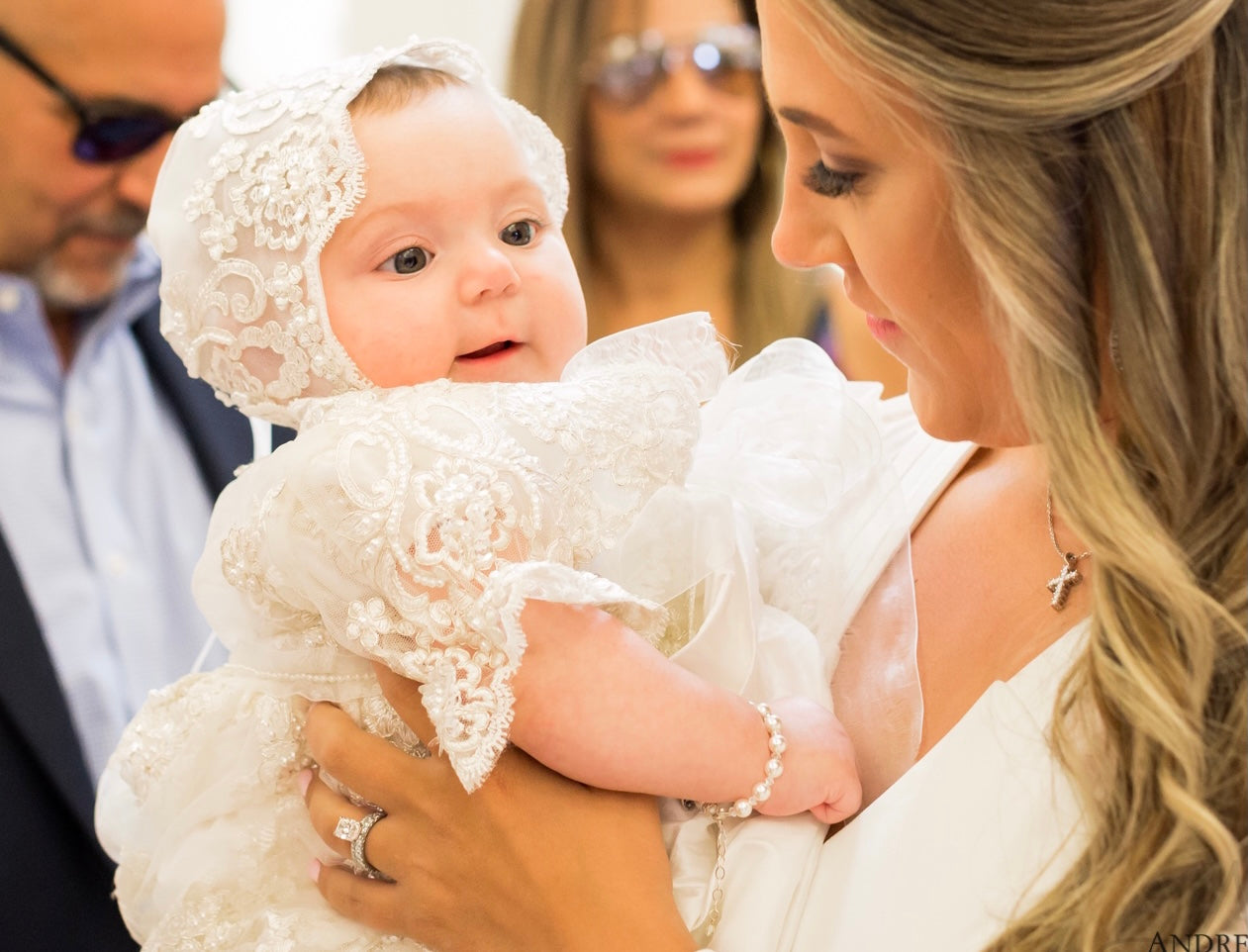 woman holding baby dressed in christie lauren baptism gown