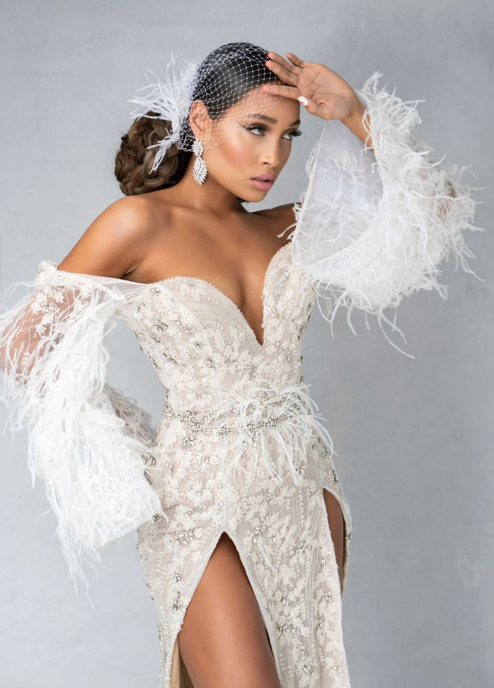 bride wearing feathered gown with christie lauren headpiece and drop earrings