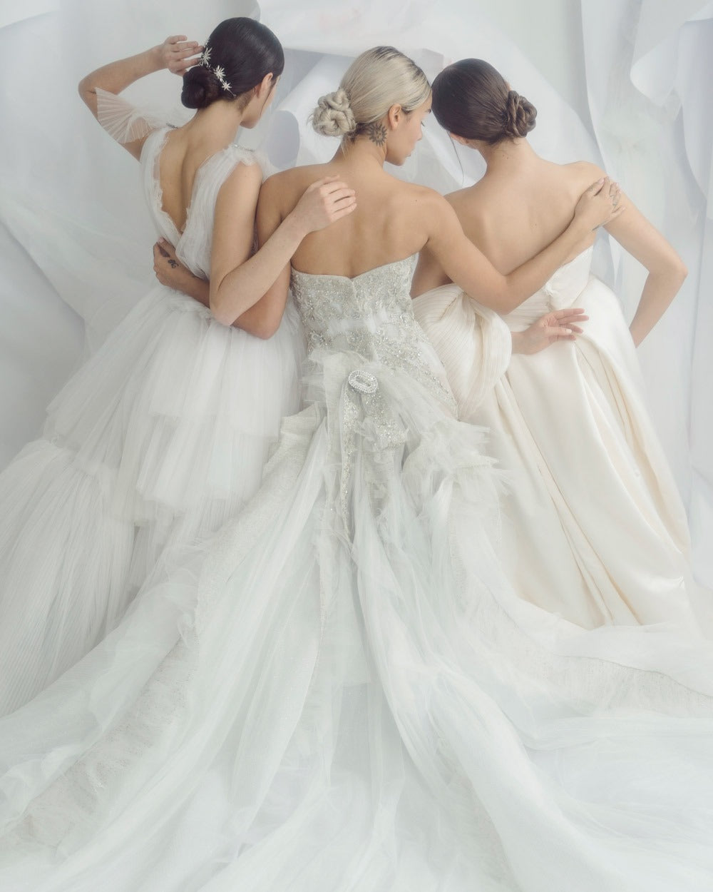 three brides pictured from back wearing christie lauren headpieces