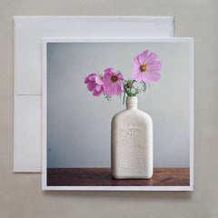 Many of us have found a love of gardening during these pandemic times!  This photograph note card shows beautiful pink flowers standing in a white bottle vase by photographer Jennifer Echols.