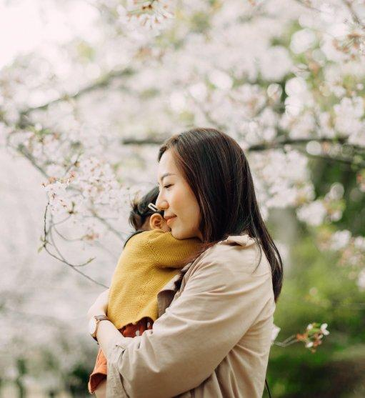 woman holding child outside near cherry blossoms