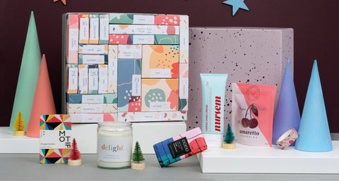 That Counts 24 Days of Gifting Advent Calendar. A few products including Nursem hand cream, a candle and a Coco chocolate bar are positioned in front of the advent calendar box itself.