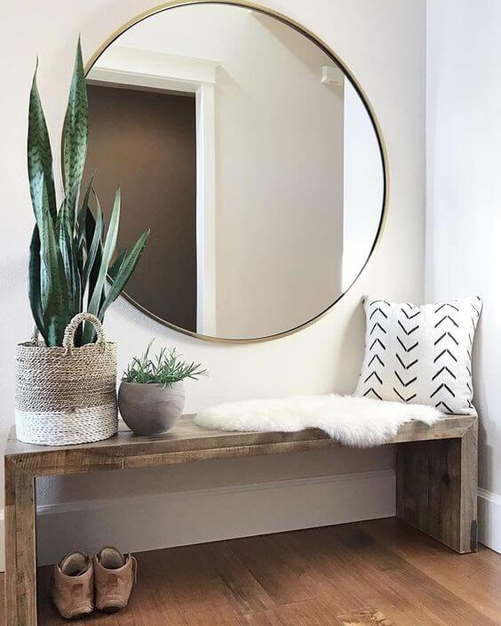 A large round mirror over top a bohemian style bench with a fur rug, plants and a throw pillow