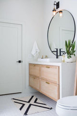 Bright white bathroom with a large circular mirror over the sink