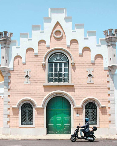 Whimsical pink building with a man on a scooter