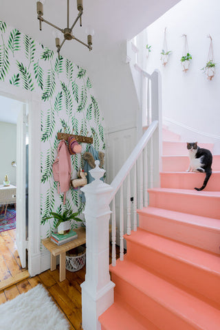 Pink ombre stairs and fern wallpaper in a stairway