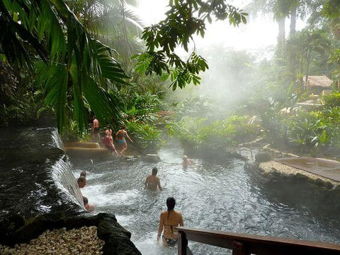 people swimming in a steaming pool in the jungle