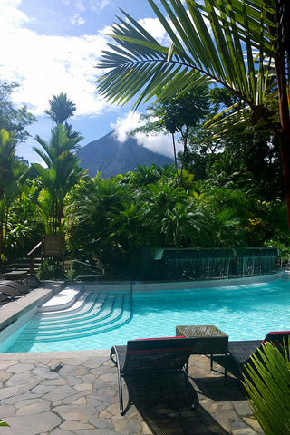 poolside with a volcano in the distance surrounded by jungle