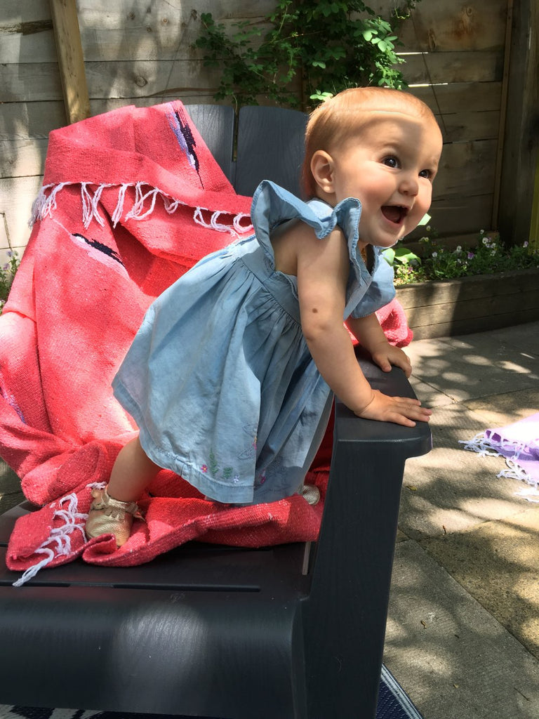 coral coloured mexican blanket on a deck chair with a baby in a blue dress