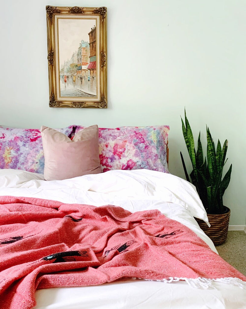 bedroom with multicoloured pillows and a coral thunderbird blanket draped over the end of the bed. A snake plant in a woven basket sits in the corner.