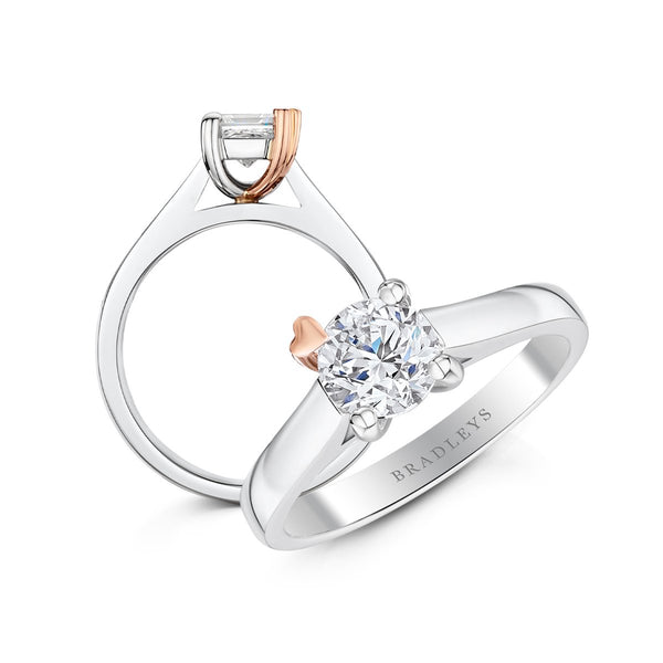 two angles of diamond engagement ring with a rose gold heart on one claw