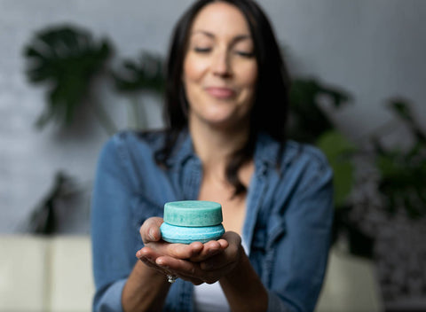 Solid Roots' Founder, Dr. Sheena Scruggs holds solid shampoo and conditioner bars