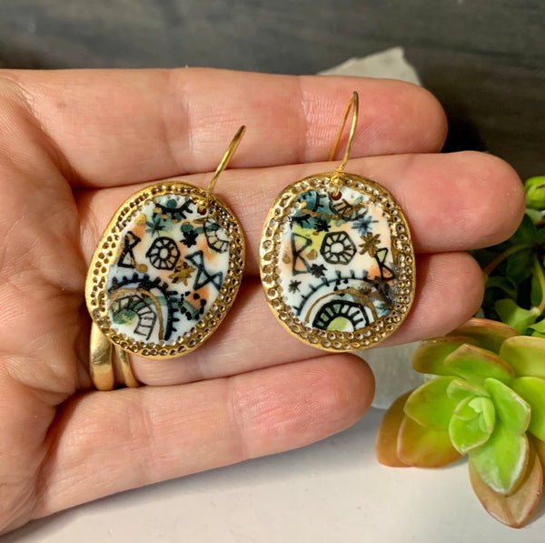 'Stars and cells' design earrings with gold border
