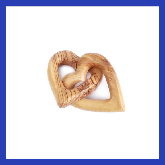two intertwined natural olive wood hearts handmade by carpenters in Bethlehem.