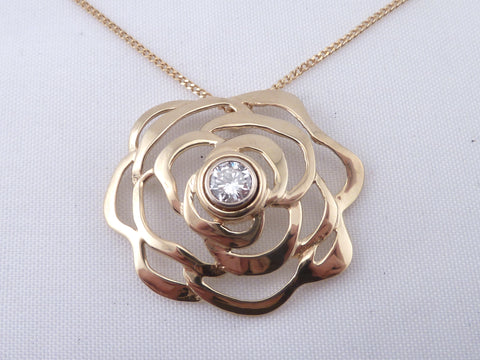 an 18 K yellow gold abstracted flower pendant with diamond center.