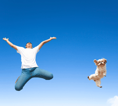 Man and dog jumping in the air together.
