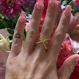 Woman wearing a gold crisscross pave ring