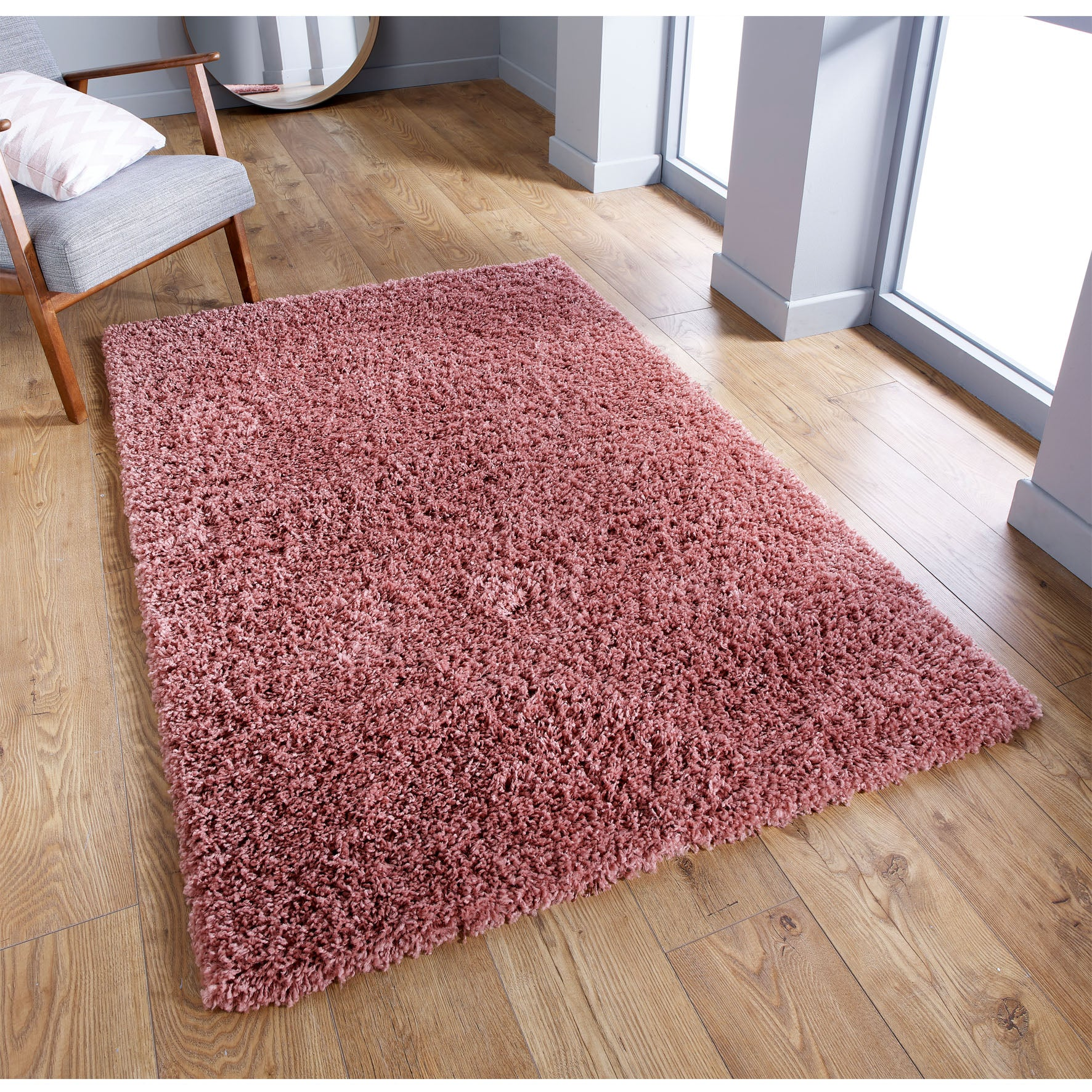 Pink rug next to chair in living room on wooden floor